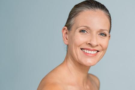Retrato de una mujer mayor sonriente que mira la cámara. Primer rostro de mujer madura después de un tratamiento de spa aislado sobre fondo gris. Concepto anti-envejecimiento. Foto de archivo