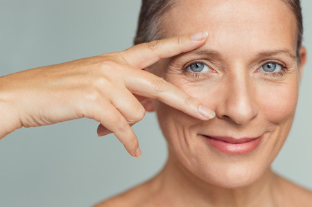 Portrait of smiling senior woman with perfect skin showing victory sign near eye on grey background.  Closeup face of mature woman showing successful results after anti-aging wrinkle treatment. Beauty mature skin care concept. Stock Photo