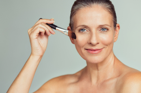 Closeup portrait of mature woman applying tonal foundation on face with makeup brush. Smiling senior woman applying powder for make up. Cosmetics and make-up portrait.