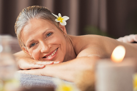 Beautiful mature woman lying on front on a massage table and looking at camera. Portrait of senior woman for a beauty treatment in a spa center. Skin care and body massage concept. Stock Photo