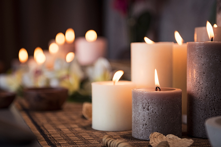 Closeup of burning candles spreading aroma on table in a spa room. Beautiful composition with grey and white candles for spa treatment. Zen and relax concept.