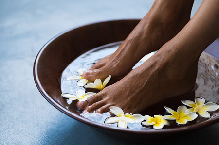 Woman soaking feet in bowl of water with floating frangipani flowers at spa. Closeup of a female feet at wellness center on pedicure procedure. Woman feet in spa wooden bowl with exotic white flowers.