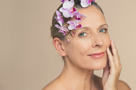 Portrait of beautiful senior woman looking at camera with a flower on head. Closeup face of beauty mature woman holding purple orchid isolated on grey background. Mature skin face with wrikles eyes.