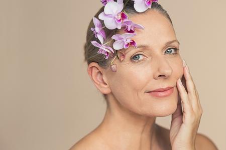 Ritratto di bella donna senior che guarda l'obbiettivo con un fiore sulla testa. Fronte del primo piano della donna matura di bellezza che tiene orchidea viola isolata su fondo grigio. Viso dalla pelle matura con occhi di wrikles.