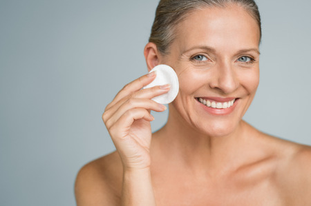Healthy mature woman removing makeup from her face with cotton pad isolated on grey background. Beauty portrait of happy woman cleaning skin and looking at camera.