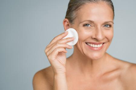 Donna matura in buona salute, rimuovere il trucco dal viso con un batuffolo di cotone isolato su sfondo grigio. Ritratto di bellezza della donna felice che pulisce la pelle e che guarda l'obbiettivo.