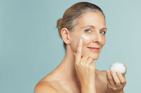 Beautiful mature woman holding jar of skin cream for face and body isolated on grey background. Happy senior woman applying anti-aging moisturizer and looking at camera. Beauty and anti aging treatmen