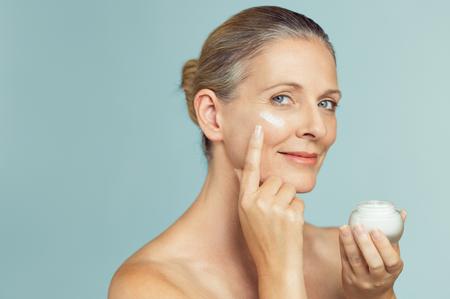 De mooie rijpe kruik van de vrouwenholding huidroom voor gezicht en lichaam dat op grijze achtergrond wordt geïsoleerd. Gelukkig senior vrouw anti-aging moisturizer toe te passen en camera te kijken. Schoonheids- en antiverouderingsbehandeling.