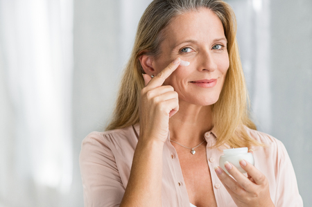 Smiling senior woman applying anti-aging lotion to remove dark circles under eyes. Happy mature woman using cosmetic cream to hide wrinkles below eyes. Lady using day moisturizer to counteract the aging of the skin.