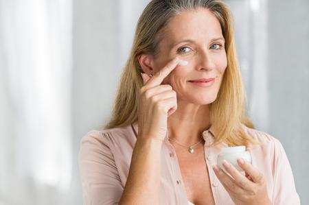 Donna maggiore sorridente che applica lozione anti-invecchiamento per rimuovere le occhiaie sotto gli occhi. Felice donna matura utilizzando crema cosmetica per nascondere le rughe sotto gli occhi. Signora che utilizza crema idratante da giorno per contrastare l'invecchiamento della pelle.