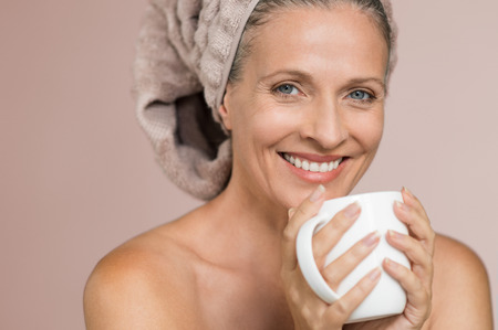 Portrait of mature smiling woman with hair covered in towel holding tea mug against grey background. Senior woman sipping infusion after shower. Happy lady with hair wrapped in towel enjoying hot beverage after spa treatment. Stockfoto