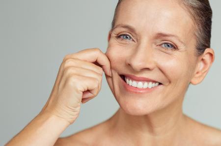 Ältere Frau, die Wangen zieht, um Weichheit zu fühlen und Kamera zu betrachten. Schönheitsporträt der glücklichen reifen Frau lächelnd mit den Händen auf der Wange lokalisiert über grauem Hintergrund. Alterungsprozess und perfektes Hautkonzept.