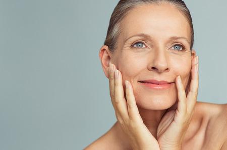 Porträt der reifen Frau mit perfekter Haut lokalisiert auf grauem Hintergrund. Nahaufnahmegesicht der glücklichen älteren Frau mit den Händen auf den Wangen, die weg schauen. Dem Altern mit einer sorglosen Haltung begegnen. Standard-Bild