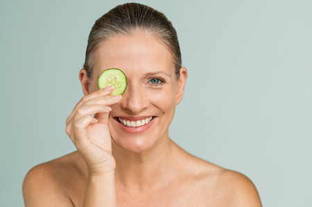 Portrait of smiling senior woman covering an eye with a cucumber slice isolated on grey background. Beauty mature woman holding slice of cucumber and looking at camera. Skincare and facial treatment.