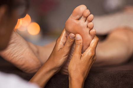 Closeup of masseuse doing foot reflexology to woman at spa. Therapist hands doing foot massage at wellness center. Woman receiving a feet massage at health spa. Stock Photo