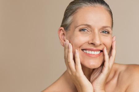 Schoonheid portret van volwassen vrouw lachend met hand op gezicht. Close-upgezicht van gelukkige hogere vrouw die zich fris voelt na anti-verouderingsbehandeling. Glimlachende schoonheid die naar de camera kijkt terwijl ze haar perfecte huid aanraakt.