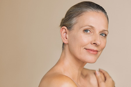 Smiling senior woman with bun hair and hand on naked shoulder. Portrait of beauty mature woman isolated over grey background with copy space looking at camera. Body and skin care concept. Stockfoto - 104902228