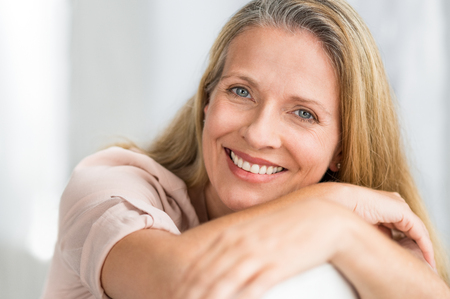 Portrait of happy senior woman relaxing on sofa. Closeup face of mature blonde woman smiling and looking at camera. Retired lady in casual leaning on couch. Stock Photo