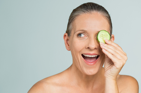 Portrait of mature beautiful naked woman smiling hiding eye behind cucumber slice. Beauty portrait of a smiling senior woman isolated on gray background. Funny senior woman in a playful mood covering