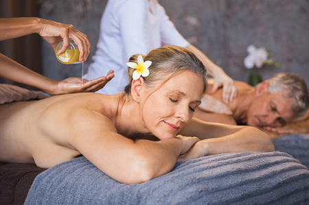 Senior couple having oil ayurveda spa treatment at wellness center. Beautiful mature woman having a back massage with her husband. Relaxed woman and man enjoying a spa beauty treatment with an oil massage.