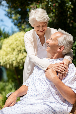 Senior woman hugging man in medical cloth in the hospital garden. Loving wife embracing old hospitalized husband sitting on bench at outdoor lawn. Caring wife supporting husband in illness in a privat