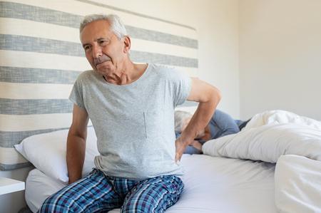 Uomo maggiore che soffre di mal di schiena a casa mentre la moglie dorme sul letto. Uomo anziano con mal di schiena che ha difficoltà ad alzarsi dal letto. Soffre di mal di schiena e stare seduti a letto la mattina.