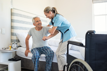 Glimlachende verpleegster die hogere mens bijstaat om uit bed op te staan. Zorgzame verpleegster die de patiënt ondersteunt bij het opstaan uit bed en thuis naar de rolstoel toe beweegt. Helpen bejaarde gehandicapte man opstaan in zijn slaapkamer.