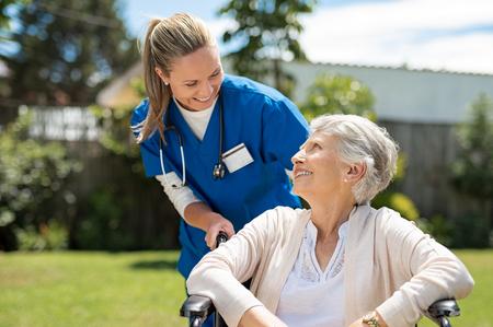 Enfermera cuidando a anciana en silla de ruedas al aire libre. Médico amable que se preocupa por la anciana discapacitada en silla de ruedas. Feliz anciana con su cuidador en el parque del hogar de ancianos. Foto de archivo