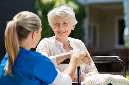 Smiling senior patient sitting on wheelchair with nurse supporting her. Doctor looking at elderly patient on a wheelchair in the garden. Nurse holding hand of mature woman outside pension home. Stock Photo