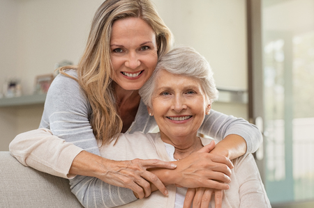 Cheerful mature woman embracing senior mother at home and looking at camera. Portrait of elderly mother and middle aged daughter smiling together. Happy daughter embracing from behind elderly mom sitting on sofa.