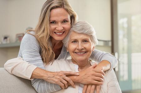 Fröhliche reife Frau, die ältere Mutter zu Hause umarmt und Kamera betrachtet. Porträt der älteren Mutter und der Tochter mittleren Alters, die zusammen lächeln. Glückliche Tochter, die von hinten ältere Mutter umarmt, die auf Sofa sitzt. Standard-Bild
