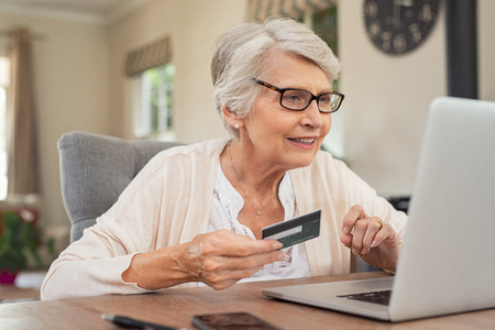 Happy senior woman making online payments using laptop. Smiling old grandmother doing shopping on ecommerce with credit card. Pensioner holding debit card for internet banking. Stock Photo