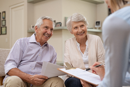 Senior couple meeting real estate agent at home. Old husband and wife with financial advisor for investment opportunities. Happy elderly man and woman listening to various investment plans for their retirement. Stock Photo