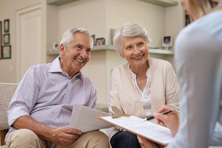 Senior paar vergadering onroerende goederenagent thuis. Oude man en vrouw met financieel adviseur voor investeringsmogelijkheden. Gelukkig oudere man en vrouw luisteren naar verschillende investeringsplannen voor hun pensioen.