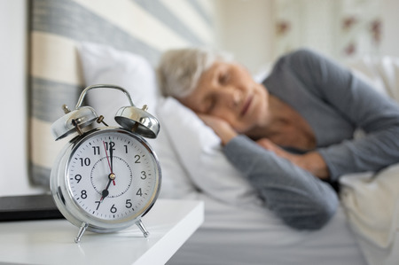 Closeup of alarm clock with senior woman in deep sleep at home. Old woman sleeping in bed next to alarm clock in morning. Elderly woman sleeping in bedroom peacefully. Stock Photo