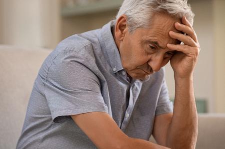 Nachdenklicher älterer Mann, der auf Couch sitzt. Deprimierter trauriger Mann, der mit Hand auf Kopf sitzt und denkt, während er wegschaut. Älterer Mann, der an Alzheimer leidet. Standard-Bild
