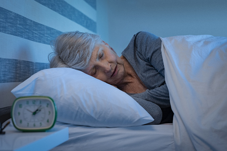 Old woman in grey hair sleeping peacefully at night time in bed. Senior woman lying on side and sleeping at home. Mature woman feeling relaxed at home while sleeping at night. Stock Photo