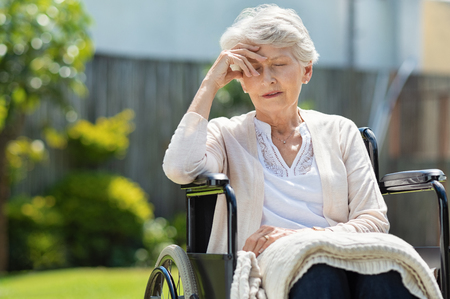 Sad senior woman sitting in wheelchair outside a nursing home. Depressed disabled lady with terrible headache. Solitude and abandon concept.