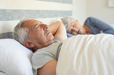Senior man and woman sleeping on bed. Mature couple resting with eyes closed during the morning. Old husband and wife sleeping together in their bed with peace. 版權商用圖片