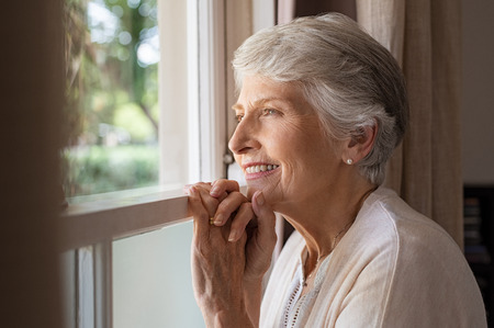 Happy senior woman standing at window and looking outside. Beautiful grandmother smiling while looking through the window. Portrait of cheerful old woman relaxing in home while standing at window sill 스톡 콘텐츠