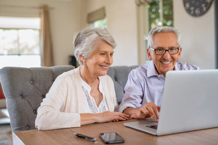 Happy smiling retired couple using laptop at home. Cheerful elderly man and old woman using computer while sitting at table. Smiling pensioner showing woman notebook at home.