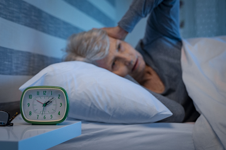 Old woman suffering from migraine unable to sleep during the late night. Elderly woman in bed ill and suffering from sleeplessness and insomnia. Closeup of alarm clock showing time with senior woman unable to sleep in background.