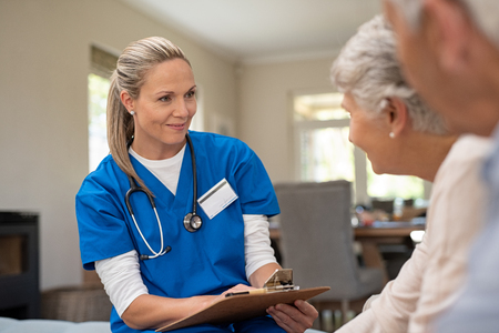 Happy nurse talking to senior patients in private clinic. Senior couple consulting health and medical report with doctor at home. Old man and elderly woman visiting the nurse with clipboard and health issues.