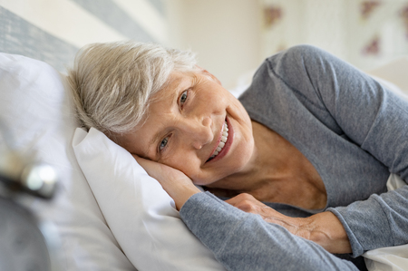 Smiling senior woman resting on bed and looking at camera. Awaken old woman with grey hair and pajamas in the early morning light. Portrait of elderly woman lying on side on bed and smiling. Banco de Imagens