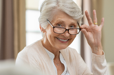 Happy retired senior woman looking at camera while holding eyeglasses. Smiling satisfied woman wearing spectacles at home. Closeup face of old grandmother trying on new eyewear. Foto de archivo
