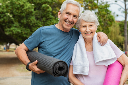 Lovely senior man and old woman holding yoga mat for exercising outdoor. Aged husband and wife ready for yoga session at park. Active healthy retired couple looking at camera before a postural session.