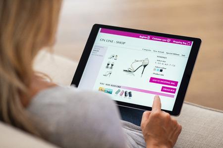 Close-up van vrouw die online het winkelen op digitale tablet thuis doet. Achteraanzicht van vrouw hand scherm aan te raken tijdens het selecteren van schoenen op e-commerce portal. Dame gebruikt e-commerce webshop om schoenen te kopen.