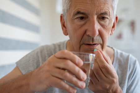 Ill senior man taking medicine for hypertension. Portrait of elderly man taking pills for depression. Old man swallowing pill with glass of water. Stock Photo