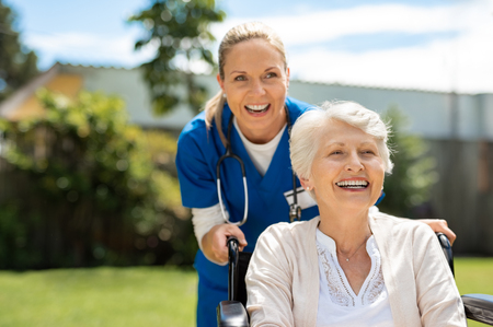 Happy nurse and elderly woman sitting in wheelchair enjoying outdoor treatment session. Beautiful nurse with laughing senior woman in wheelchair at outdoor park. Smiling disabled old lady in wheelchair at park. Stock Photo