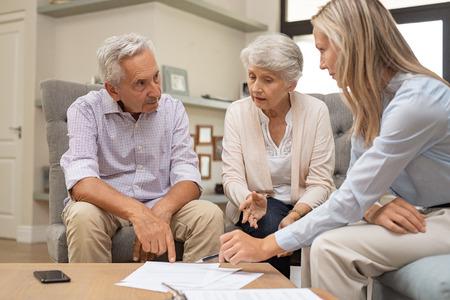 Bedrijfsagent die met een gepensioneerd stel hun toekomstige investeringsmogelijkheden plant. Financieel adviseur in gesprek met oudere man en vrouw en wijst op de contractvoorwaarden op document. Pensioenregelingen en voorwaarden.
